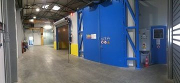 Zinc-spraying room with crane slot next to a drying booth with roll-up door